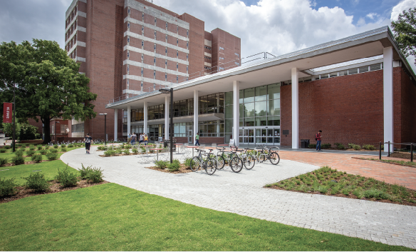 Exterior of the Hill Library, a brick building with grass, bikes, and tables in front