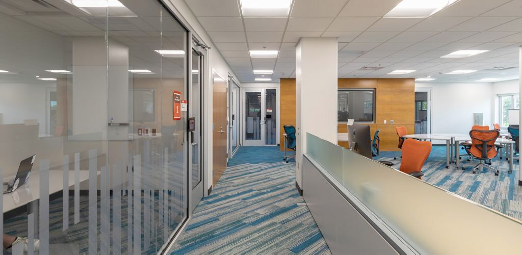 Walkway in the area of the Data Experience Lab, with study rooms to the right, a conference room and large screen straight ahead, and large open tables in the lab to the right.