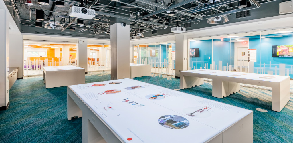 The Innovation Studio's gallery tables display interactive exhibits; above is a grid system hosting projectors, lights, and sensors.