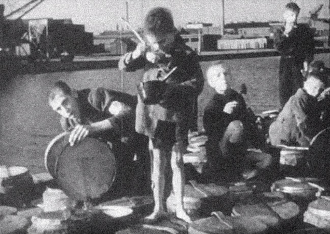 Five boys eating on dockside wharf.