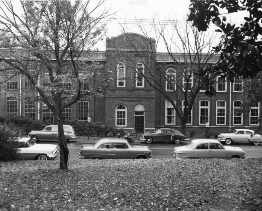Front view of Tompkins Hall, with automobiles parked on Hillsborough Street, circa 1955