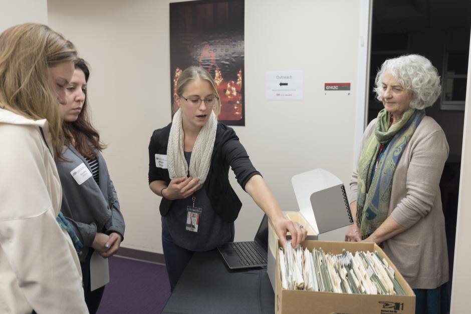 Linda Sellars and Library Associate Jessica Serrao display a box of materials before and after processing, as well as an example of an online collection guide, to illustrate the process of making materials available for researchers.