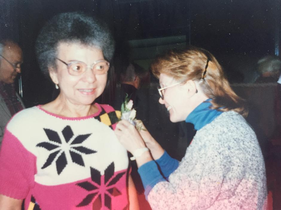 Justina Williams at her retirement party, with a corsage pinned by Dr. Trudy Mackay, 1988.