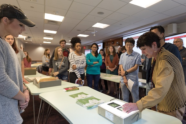 Eli Brown, Head of the SCRC, shows students the hand-colored lantern slides of B. W. Wells photo