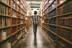 A child walks between two bookshelves