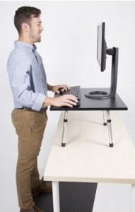 a person working on a computer at a standing desk