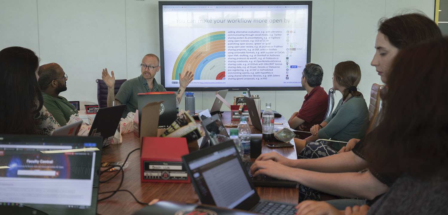 Group of people sitting around a table with laptops discussing a data visualization on a large screen