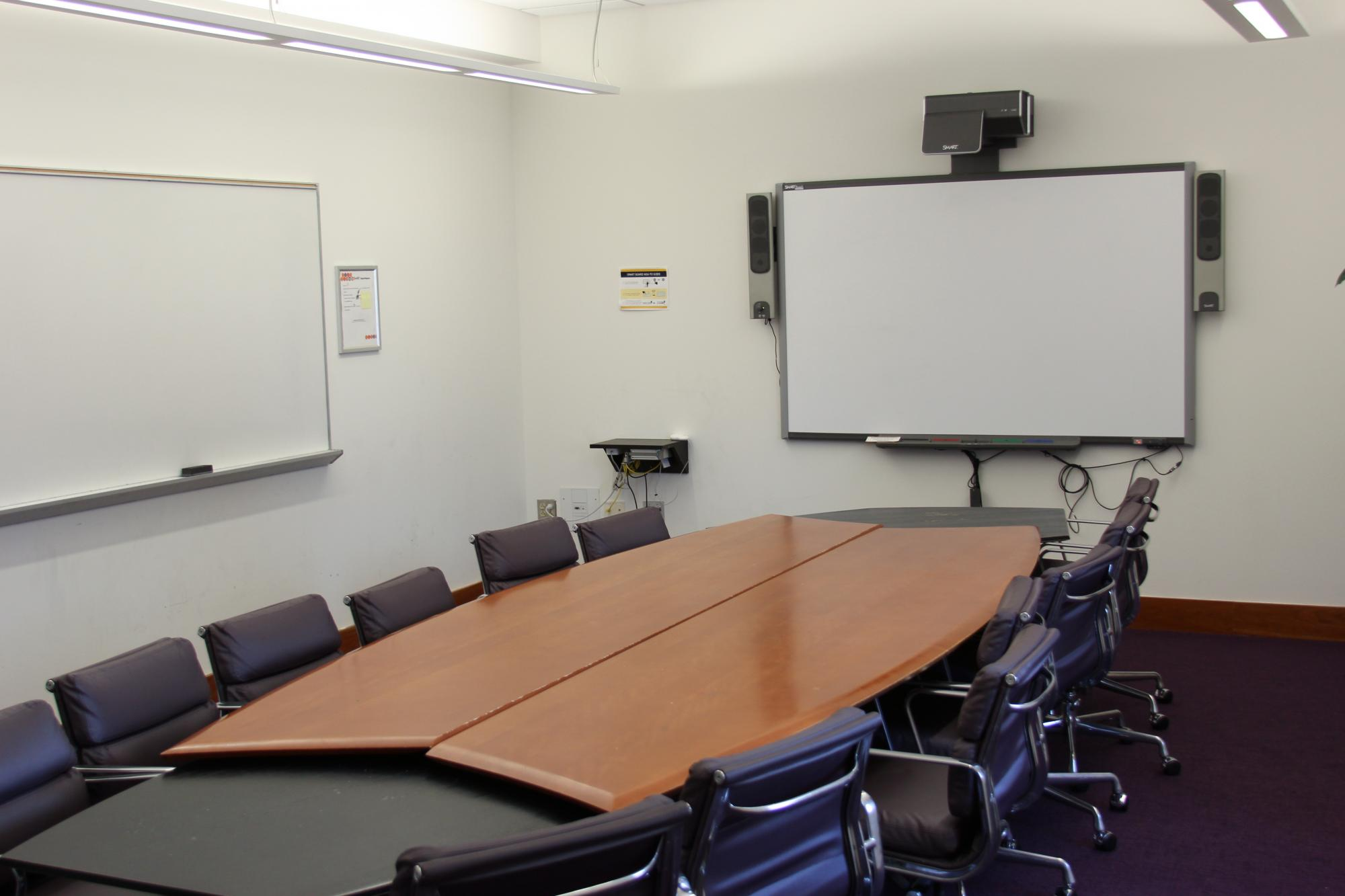 large meeting table with smartboard and whiteboard