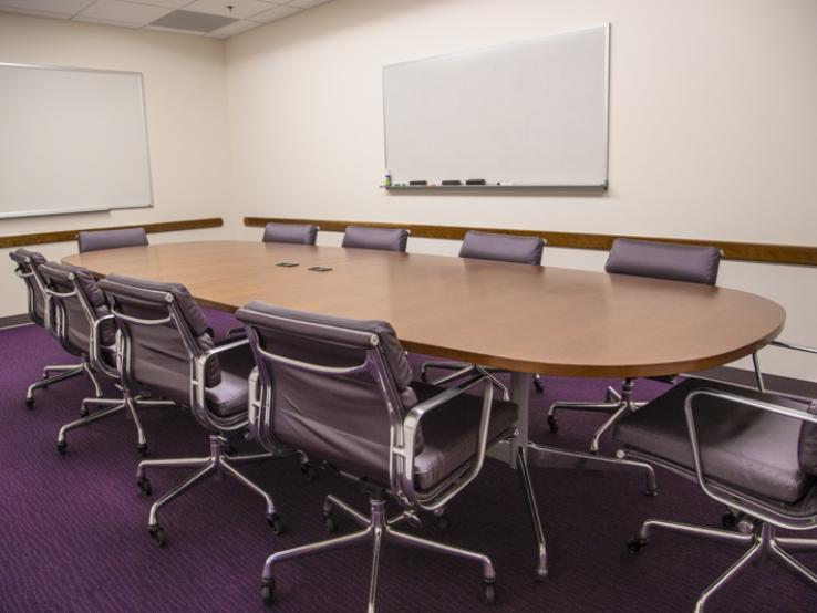 A long meeting table with a whiteboard