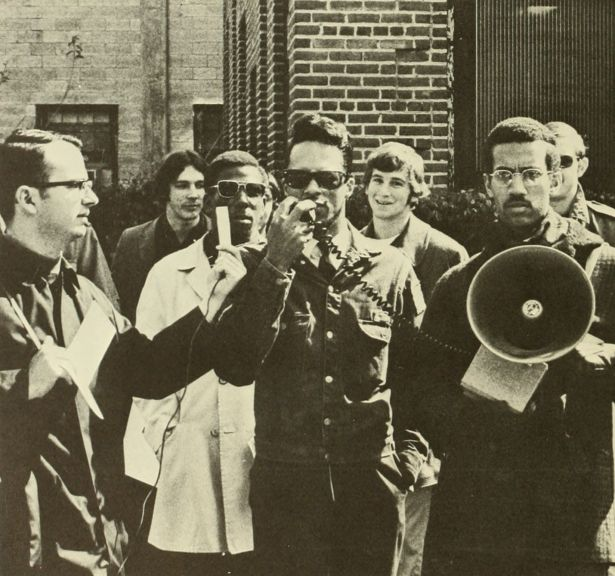 A rally supporting NC State facilities employees, 28 Feb. 1969.  Society of Afro-American Culture President Eric Moore holds the loudspeaker.  Agromeck 1969 photo.