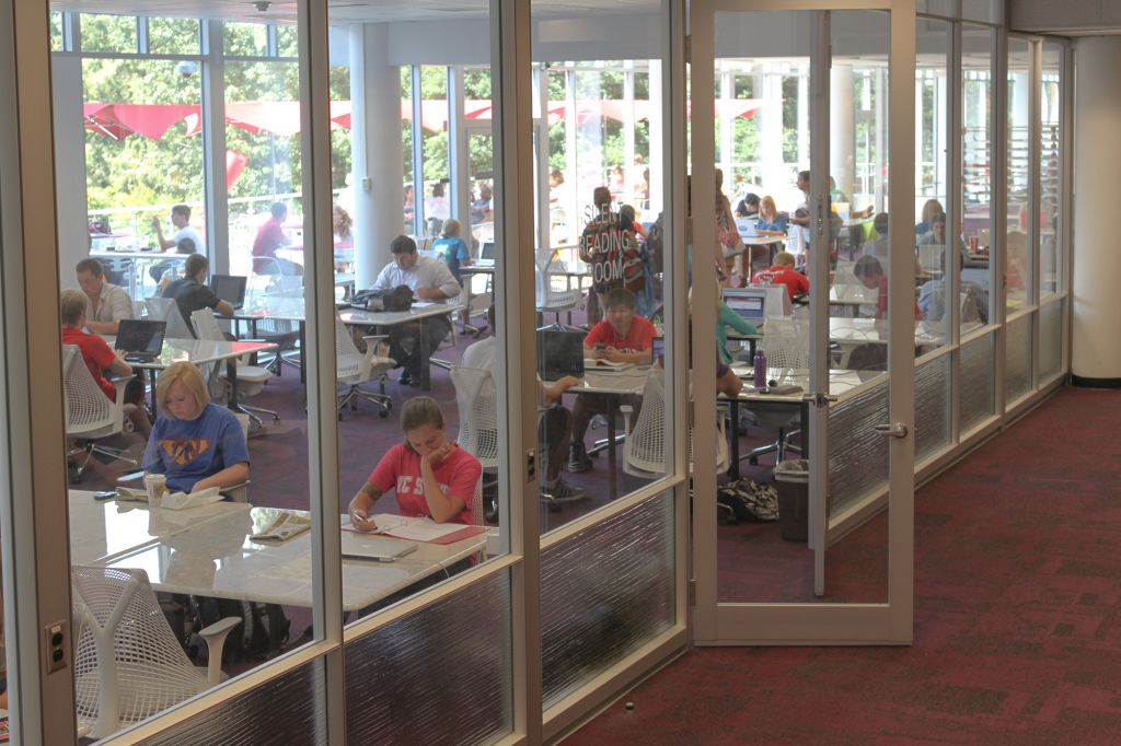 Entrance to glassed in area of Hill Library's silent reading room with students working at tables inside.