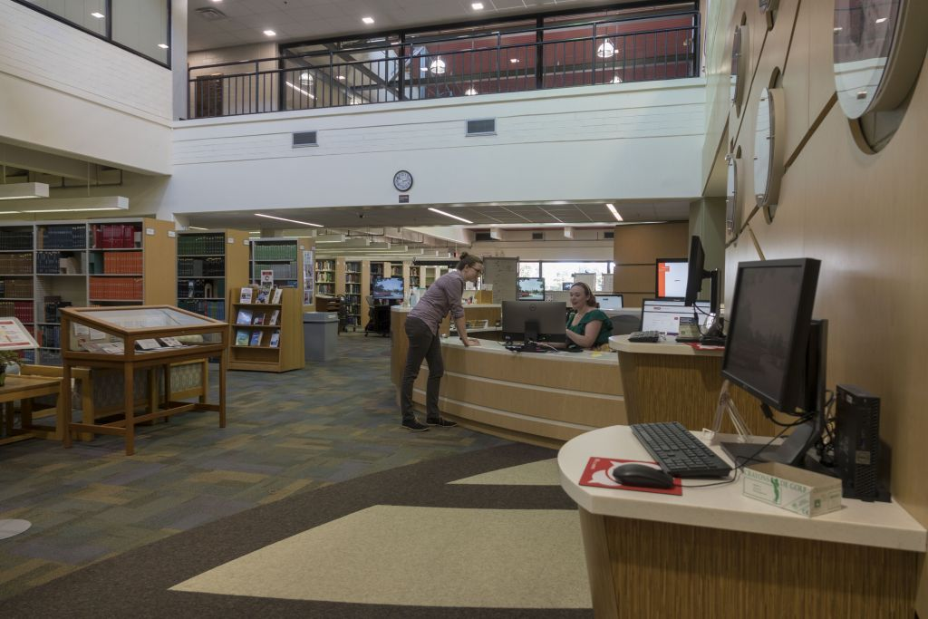 Far view of the service desk, which is set halfway through the building from the entrance to the Veterinary Medicine Library, past a lookup kiosk and exhibit case