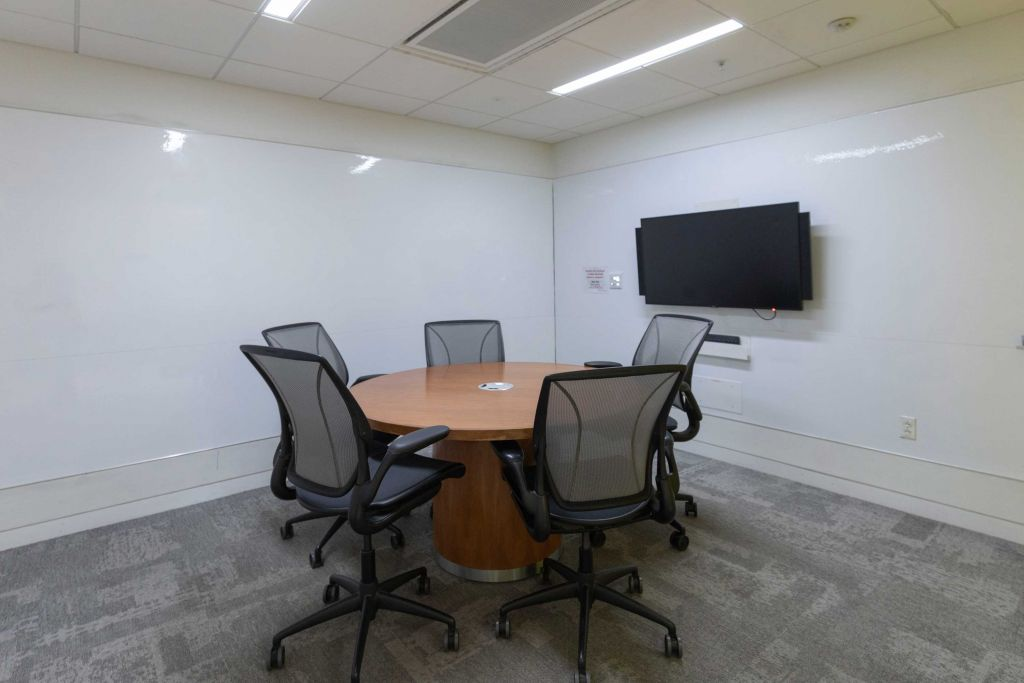 Study room with wall mounted white boards, empty round table, 5 chairs and display monitor