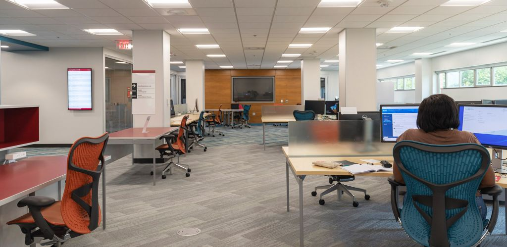 Large study space with computer workstations, large tables, and a discussion area at the back with a large screen