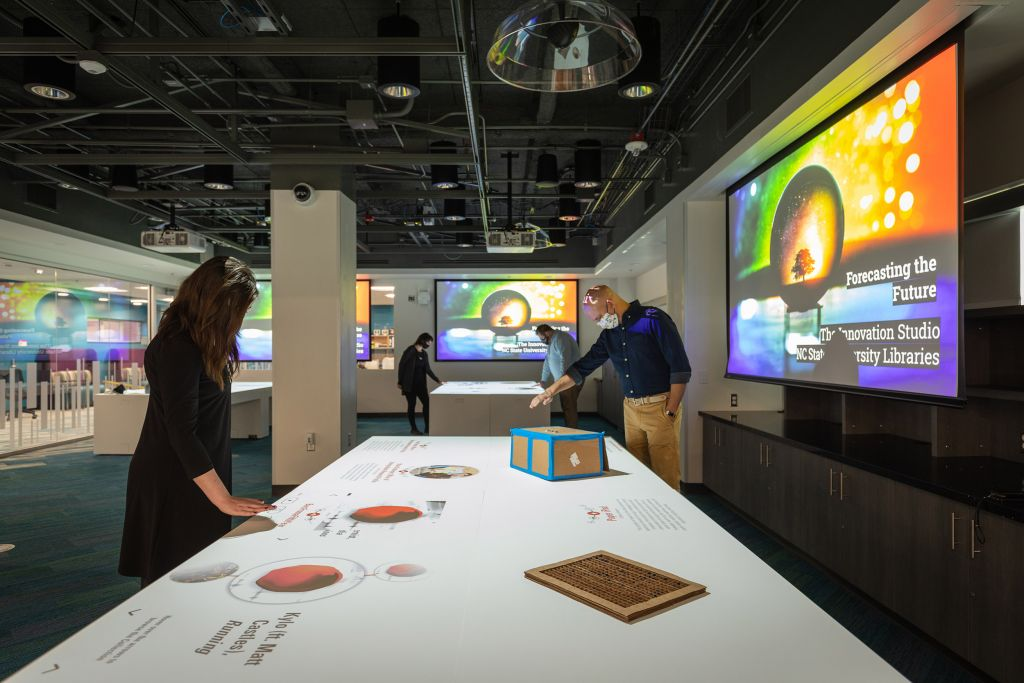 Large, darkly lit room with tables that have images projected on them and walls with screens. People hover their hands over the tables to interact with digital exhibits.