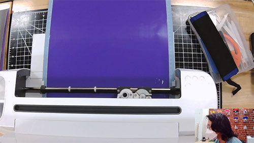 A cutting machine cuts into a purple sheet