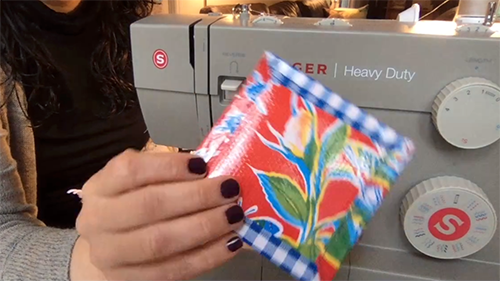 A hand holds a colorful coaster in front of a Singer sewing machine