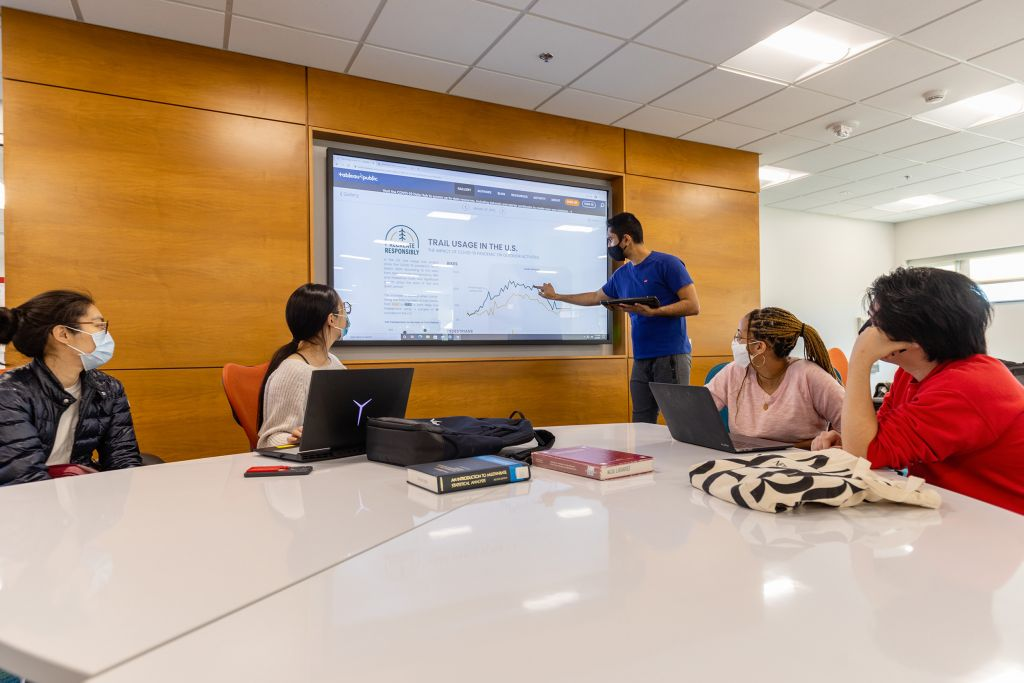 A person draws a graph on a very large touchscreen that is mounted to a wall. Four other people look on in interest