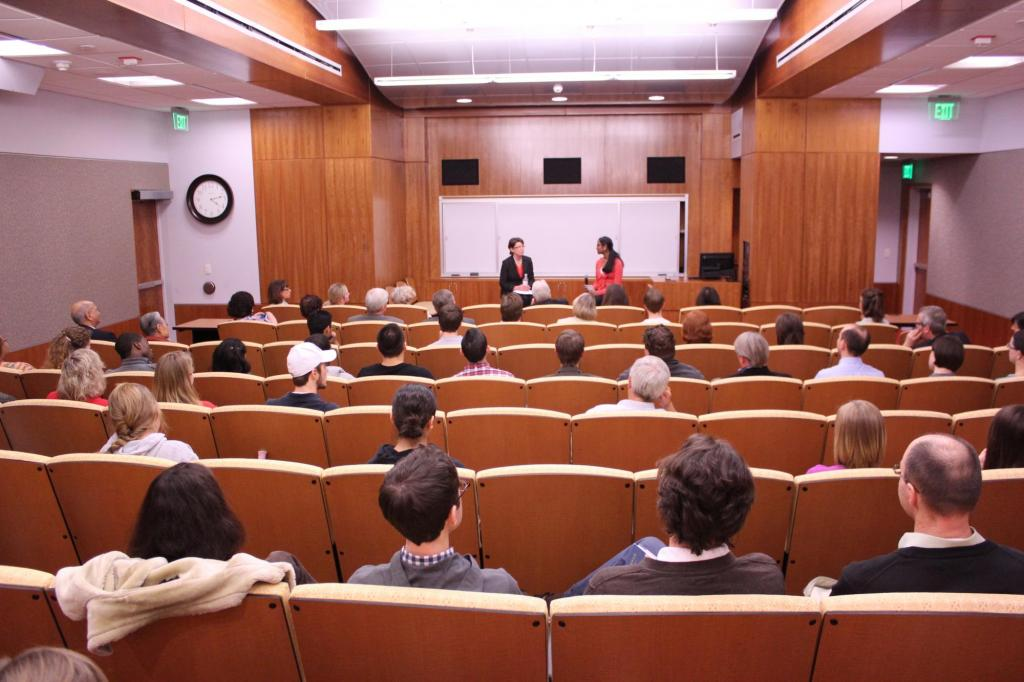 The Auditorium at Hill Library filled with students, with two people presenting at the front of the room.