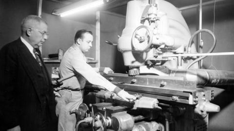 Fred Wheeler, left, supervises grinding graphite for the nuclear reactor, 1951