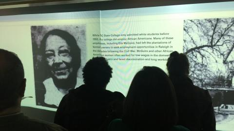 History 596 presenting the Soldiering On virtual exhibit in the DH Hill Library's Visualization Studio on 11 December 2017.  The section depicted here shows Ella McGuire, an African American who nursed NC State students during the pandemic.