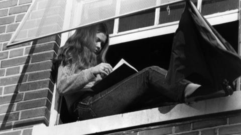 A student reads a book in her dormitory window.