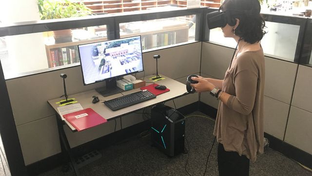 Student using Oculus Rift with touch controllers in the V R Pod