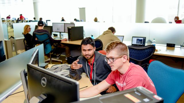 Library instructor helping patron at a computer workstation in the Hunt Library Dataspace
