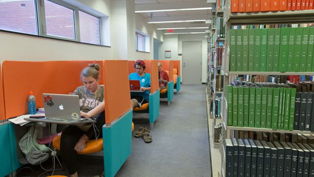 Students in carrels next to bookstacks.