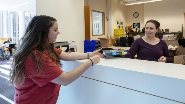A library staff member hands a book to a patron at a desk, with sunny windows in the background