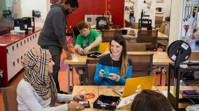 Interior of makerspace, with busy students working on electronics