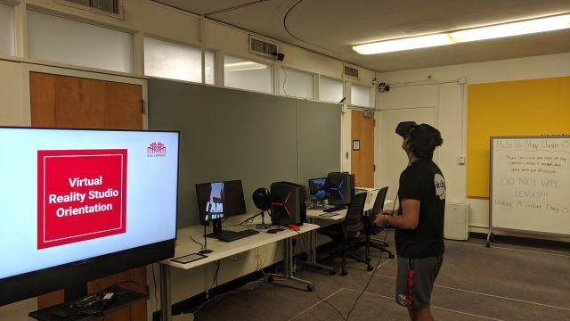 One user is standing and using an Oculus Rift V R workstation to experience a Virtual Reality program