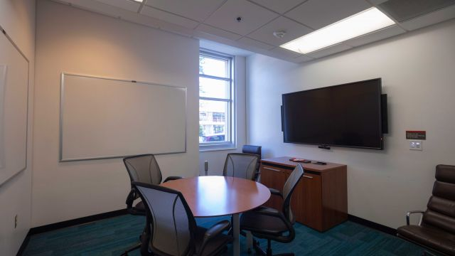 Graduate Group Study room 1 1 3 2 C work table and chairs with whiteboards on wall, large display screen, and window.