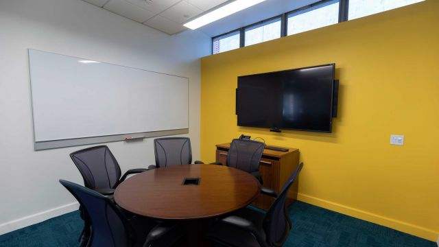 Hill Faculty Workroom 2 3 1 2 A with round work table and chairs, display screen, whiteboard, and exterior windows.