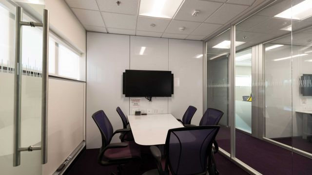 Hill Group Study room 5 4 2 4 with work table, chairs, display screen, glass walls, whiteboard wall and external windows.