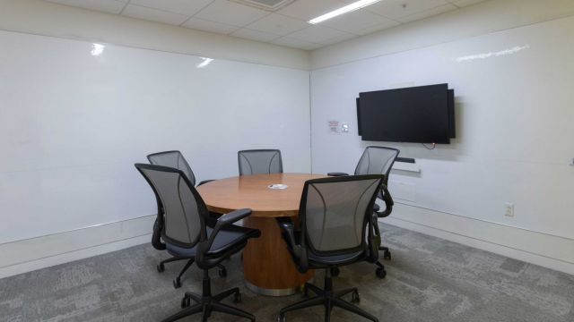Hunt Group Study room 2 3 0 5 with work table and chairs, display screen, and whiteboard walls.