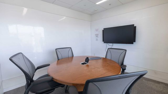 Hunt Group Study room 2 3 1 3 with work table and chairs, display screen, and whiteboard walls.