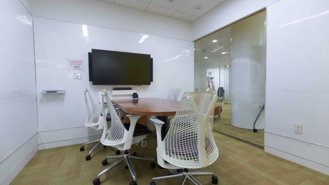 Hunt Group Study room 3 2 1 7 with work table and chairs, display screen, and whiteboard walls.