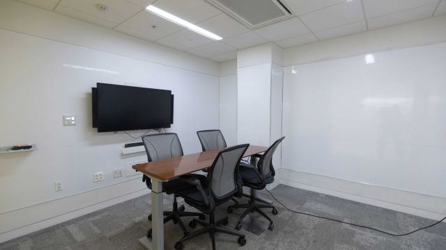 Hunt Group Study room 2 3 0 6 with work table and chairs, display screen, adjustable height table, and whiteboard walls.