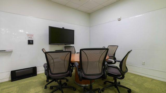 Hunt Graduate Group Study room 4 3 1 1 with work table and chairs, display screen, and whiteboard walls.