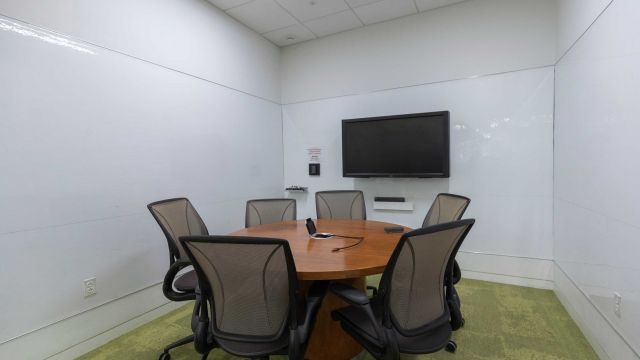 Hunt Graduate Group Study room 4 3 1 2 with work table and chairs, display screen, and whiteboard walls.