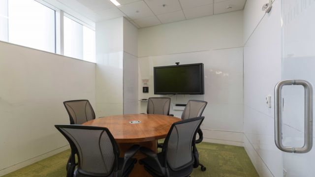 Hunt Graduate Group Study room 4 3 1 2 with work table and chairs, display screen, whiteboard walls, and exterior windows.