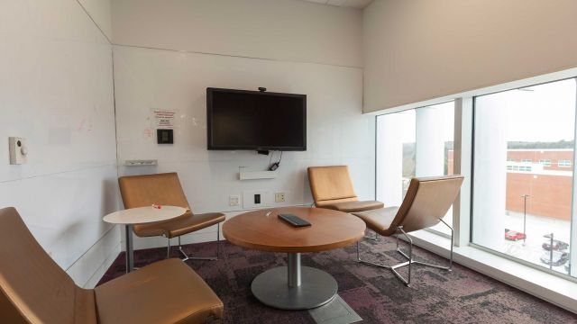 Hunt Graduate Group Lounge 4 3 2 1 with coffee table and casual seating, display screen, whiteboard walls, and exterior windows.