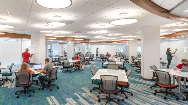 A bright, open space with students sitting at tables and standing around. Glass-walled study rooms line one wall of the space.