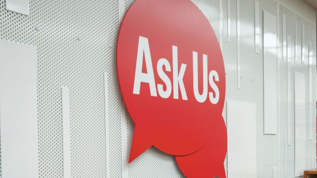 A large red speech bubble that reads, Ask Us