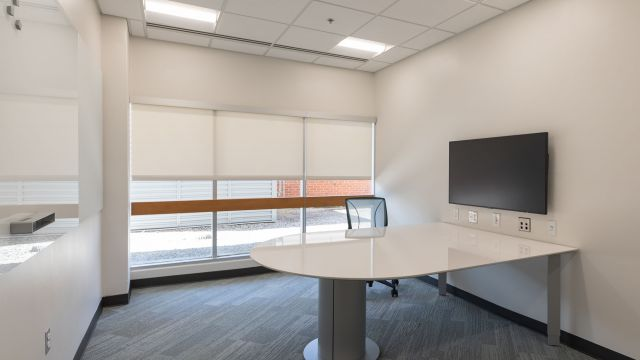 Large sunny study room with monitor, table, single office chair, whiteboard, outlets, and a big window