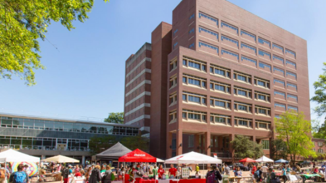 Brick exterior of the Hill Library with tents set up in the brickyard