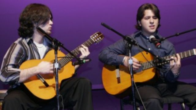Two guitarists playing a duet on stage