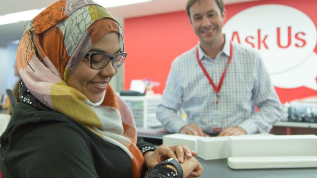 A smiling student checks their watch at the Ask Us Center desk while a librarian smiles at them