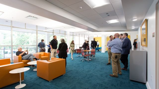 Many faculty members chatting in a bright room with modern, colorful furniture